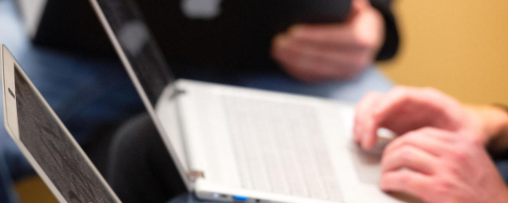 zoomed in on three sets of hands holding and typing on laptops. The focal point is of a man's hands wearing a silver watch holding a macbook pro