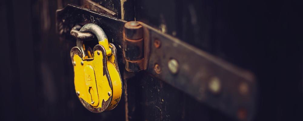 Close up of a yellow padlock on a locked door