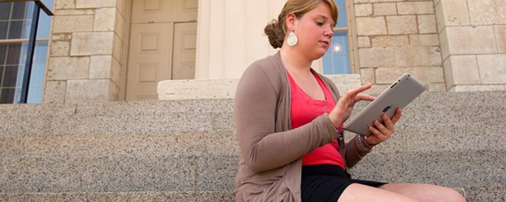 Woman uses an iPad in front of the Old Capitol.