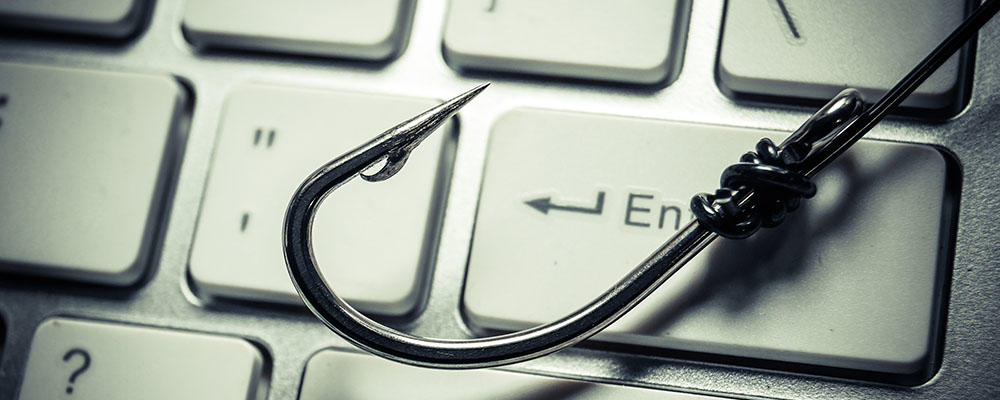Photo illustration showing a fishing hook on a computer keyboard