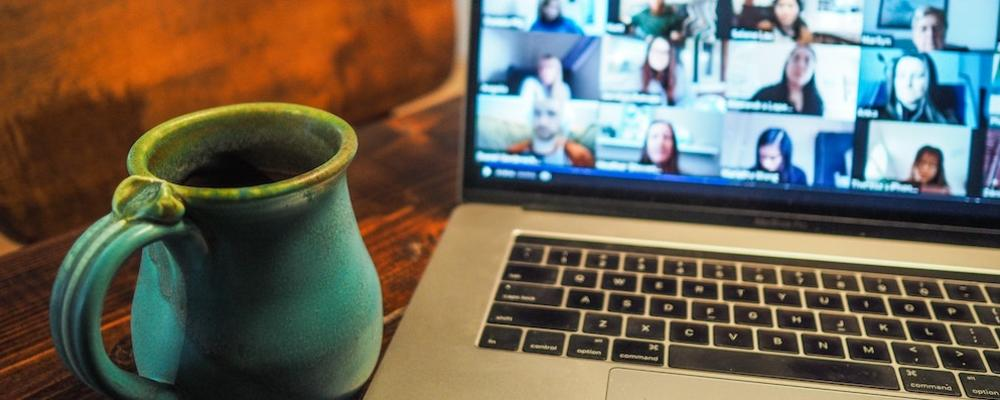 Photo of a laptop with video conference on screen and a coffee mug in the foreground