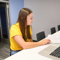 Student wearing a yellow shirt looking down at an open text book with an open laptop next to the book