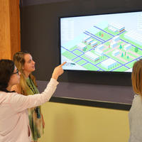3 students viewing digital signage