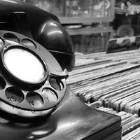 rotary dial phone sitting on top of records