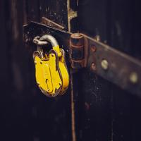 Close up of a yellow padlock on a locked door