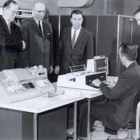 black and white picture of men in suits surrounding a man working on a type of computer