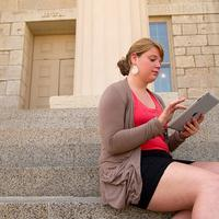 woman sitting on pentacrest steps tapping iPad